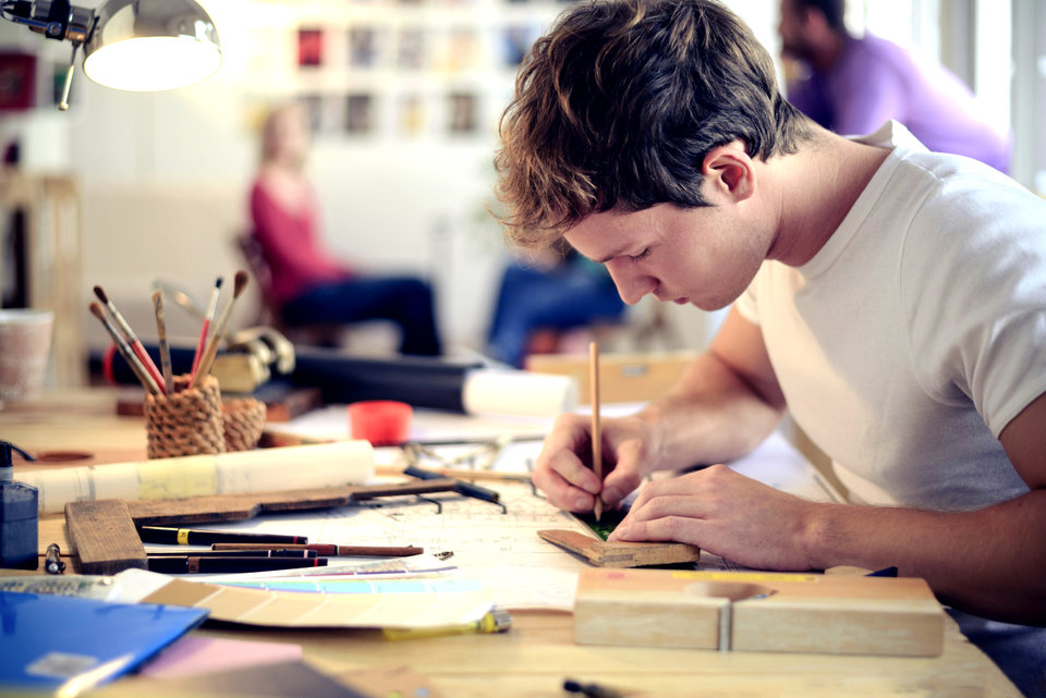 young man drawing plans
