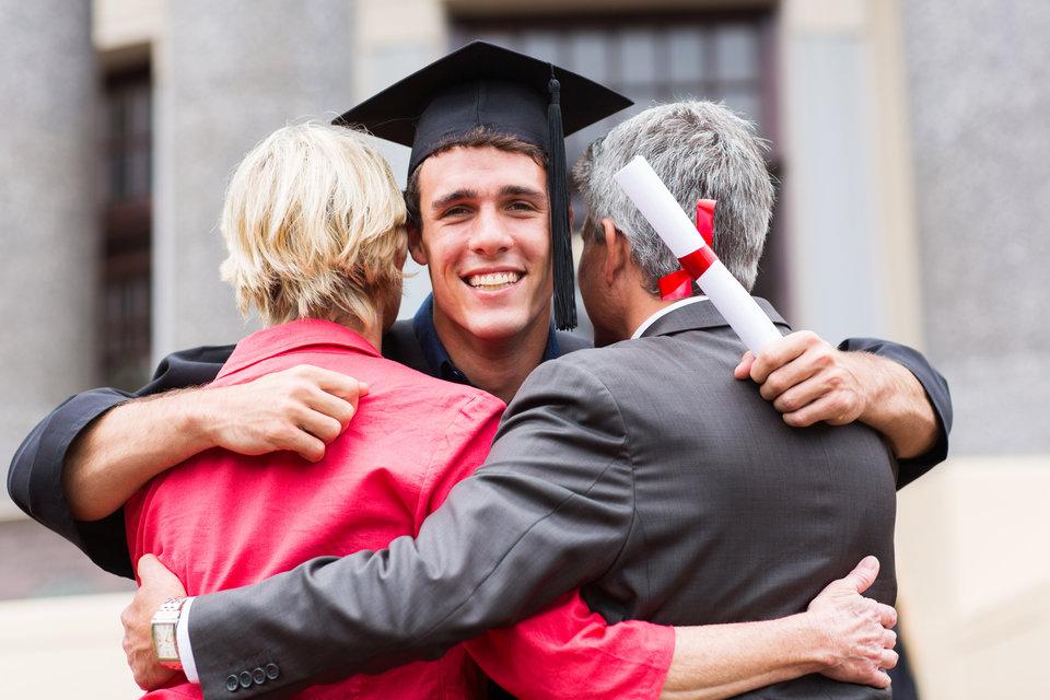 College graduate hugging parents
